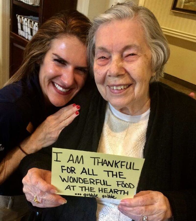 A caretaker and resident smiling, holding a piece of paper that says 'I am thankful for all the wonderful food at the hearth'