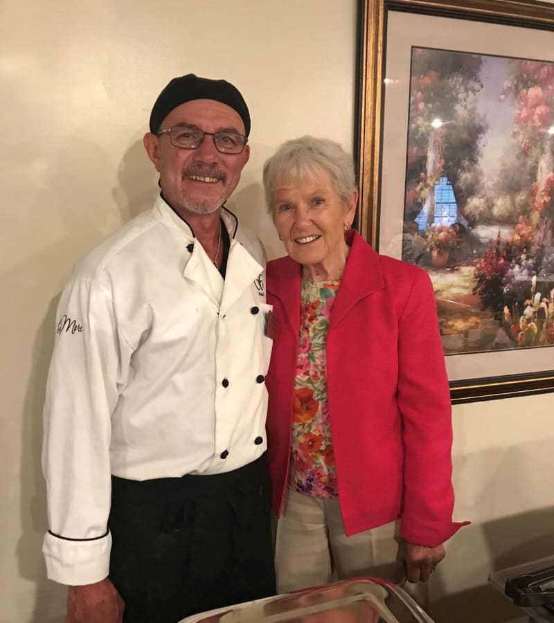 A chef and a resident arm-in-arm smiling for a photo at a Hearth Management community