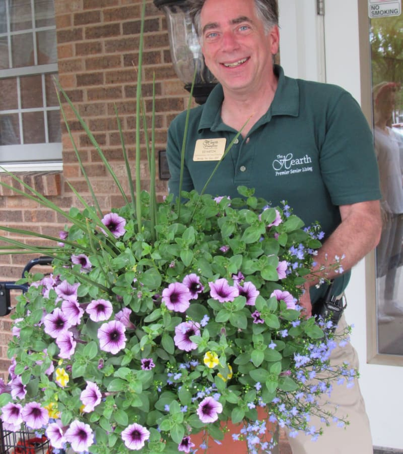 Ed H. Holding some potted flowers at a Hearth Management community
