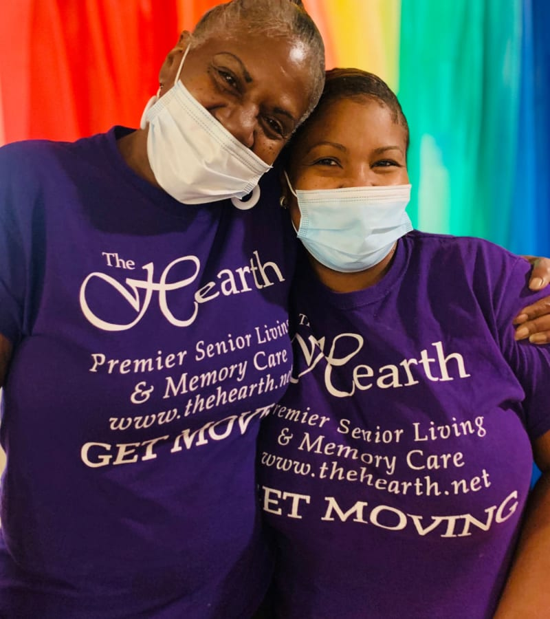 Two hearth employees hugging in front of a rainbow banner at a Hearth Management community