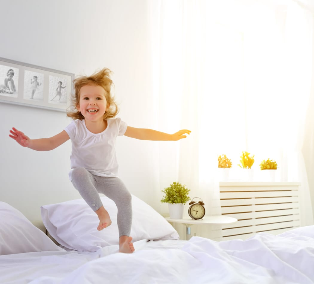 Child jumping on their bed at Briarcliff Townhomes
