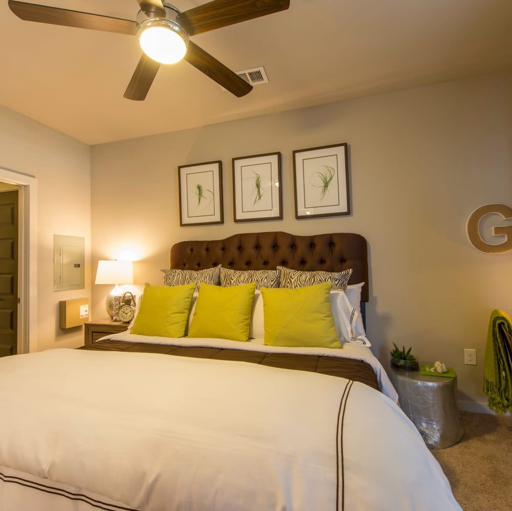 Spacious master bedroom with a ceiling fan and plush carpeting at Elite 99 West in Katy, Texas