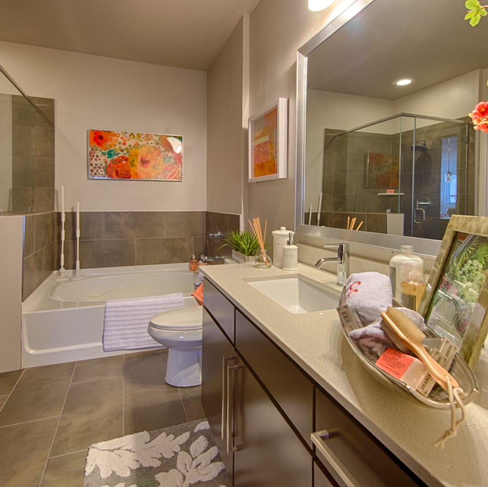 Bathroom with an oval tub and white counter tops at Elite 99 West in Katy, Texas