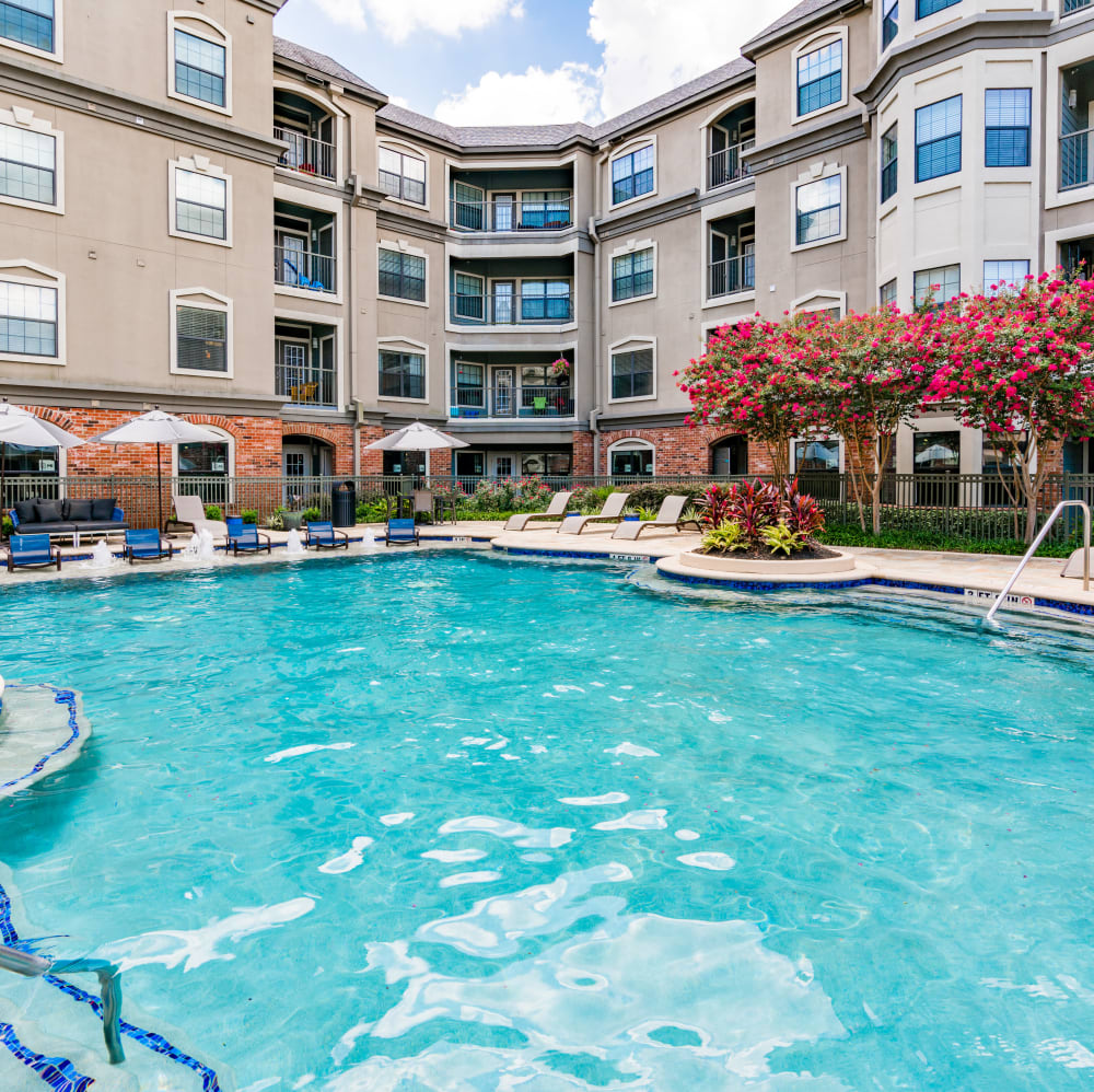 Sparkling pool with lounge chairs at The JaXon in Kingwood, Texas