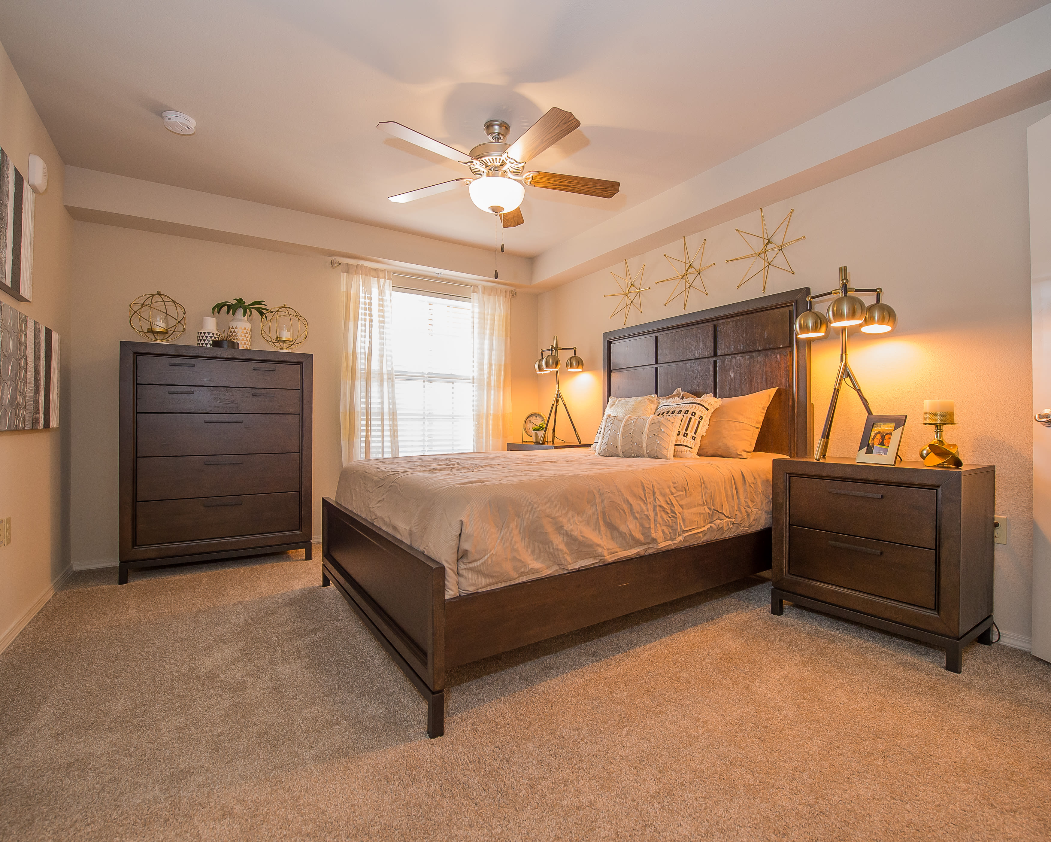 Sun-lit bedroom with ceiling fan at Portico at Friars Creek Apartments