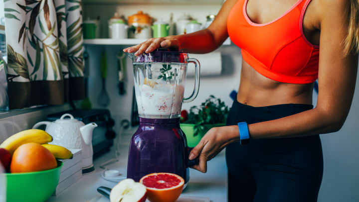 Sportswoman making a healthy smoothie on a blender.