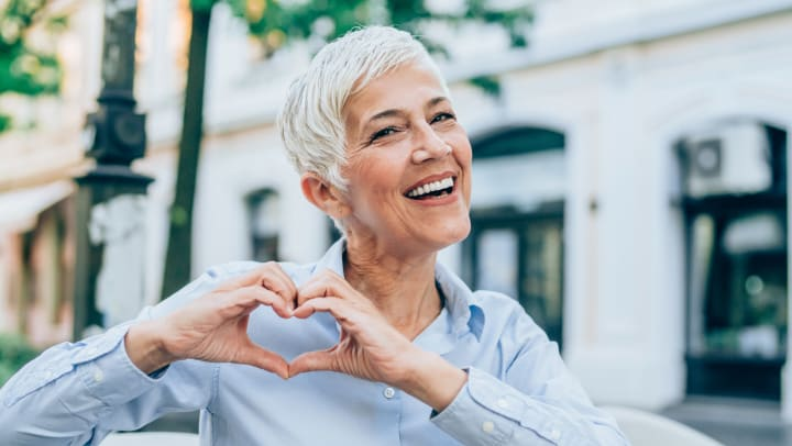 Elderly woman with heart hands similing