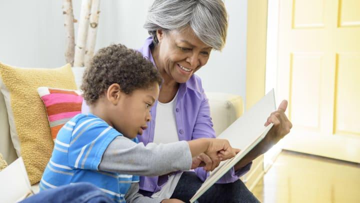 Senior woman reading book with grandchild