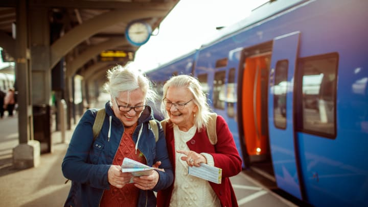 Elderly women looking at a map and smiling at a train station.