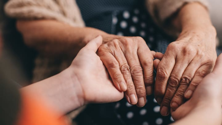 Younger person's hands embracing the hands of a senior woman.