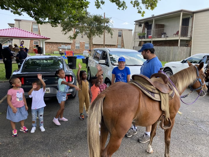 Children waiting in line to ride a pony