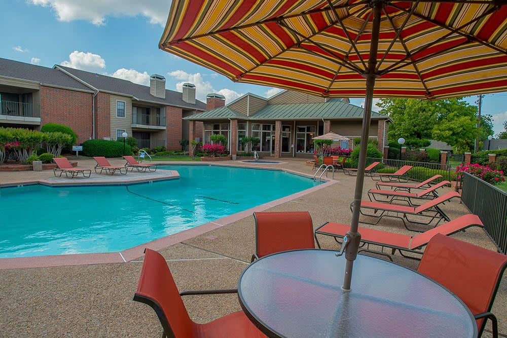 Table and umbrella poolside at Copperfield Apartments
