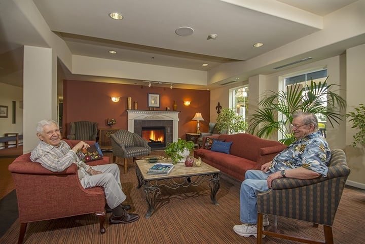 Residents relaxing near the fireplace at our senior living community in Lynnwood WA