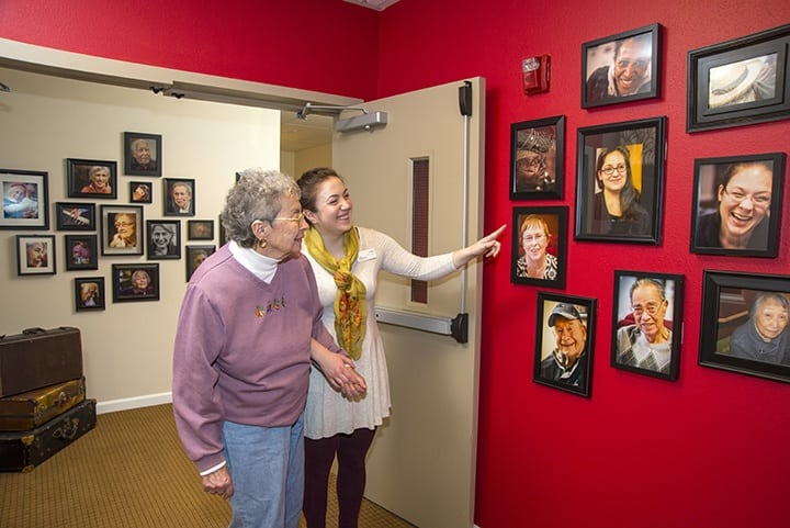 Residents looking at photos on the walls at Renton senior living