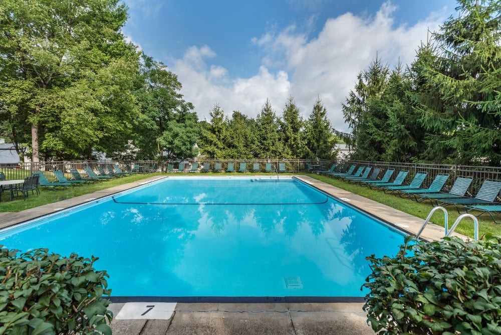 Relax next to the pool at The Cascades Townhomes and Apartments in Pittsburgh, PA