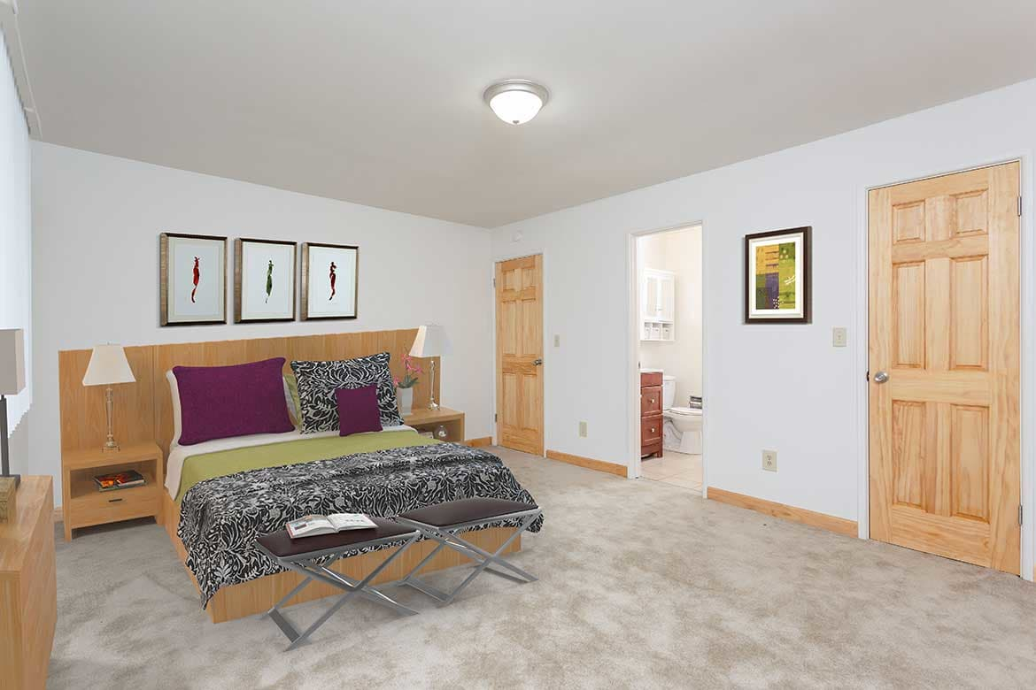 The bedroom is comfy at Meadowbrook Apartments.