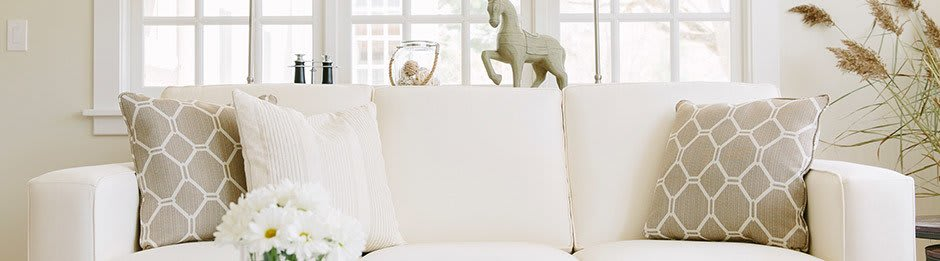 White couch with pillows and a horse