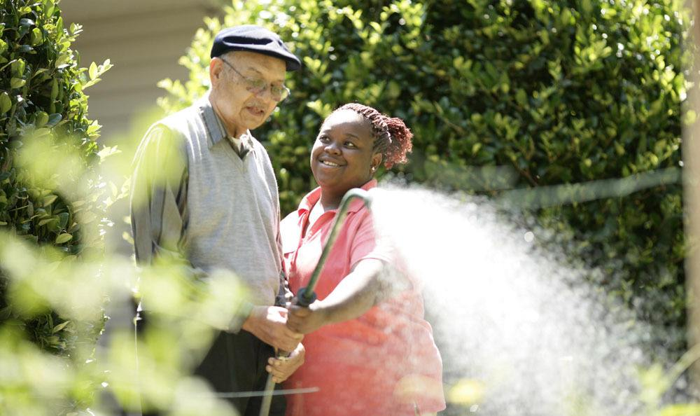 Our wonderful staff helping a resident garden our flowers at our senior living facility in {[location_city}}