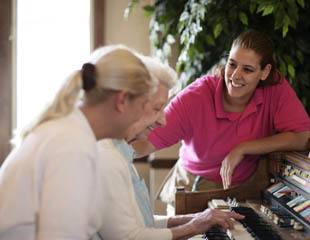Senior living residents playing piano in Sterling Heights