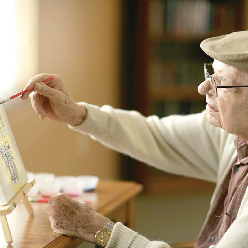 A resident paints at HarborChase senior living.
