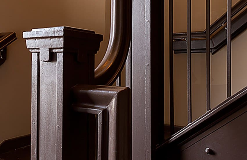 Closeup view of an interior staircase at Azalea Village Apartments, preserved and lovingly restored.