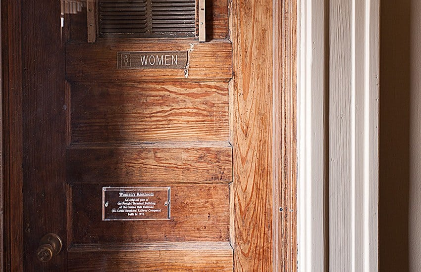 Current view of the door to the women's restroom, with the original wood and and placard explaining some of Forest Place Apartments's history.