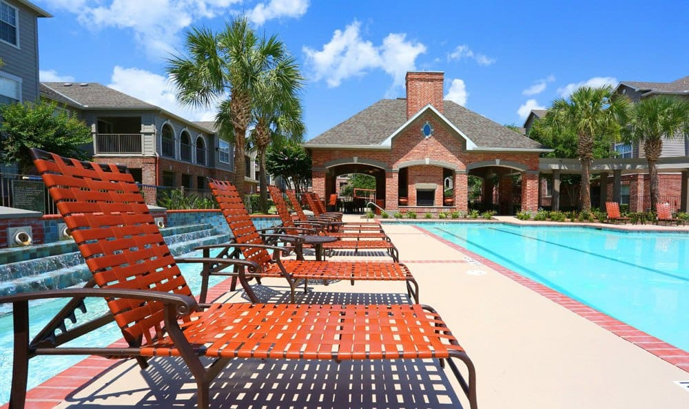 Poolside deck chairs at Southwind at Silverlake Apartments in Pearland, TX