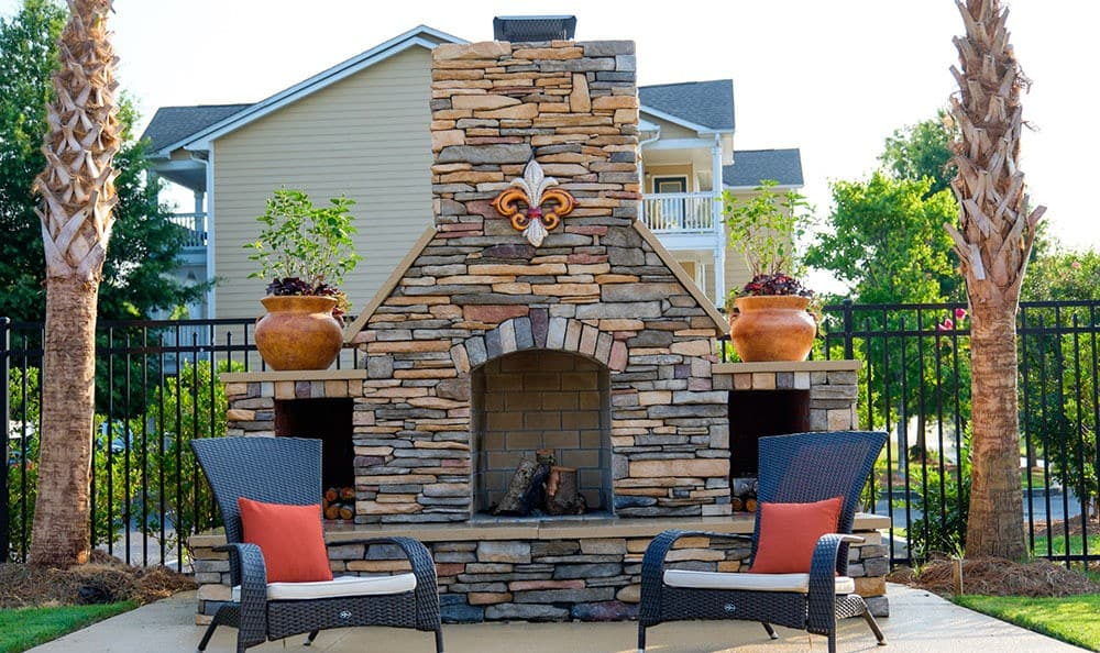 Relax next to our wood-burning outdoor fireplace at Palmetto Pointe