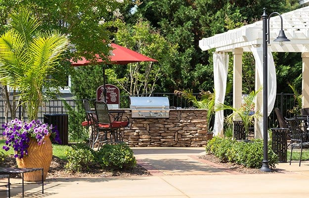 View of the firepit and outdoor barbecue area here at The Seasons at Umstead luxury apartments
