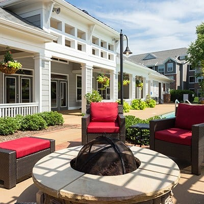 The lounge are adjacent to the pool has fire pits, comfy chairs, and more here at The Seasons at Umstead