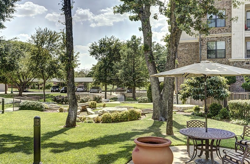 Unmatched serenity can be found in this outdoor green space, nestled under a large tree at Conservatory At Keller Town Center.