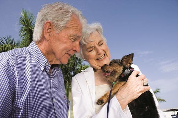 A couple with their dog at our senior living facility in The Woodlands.