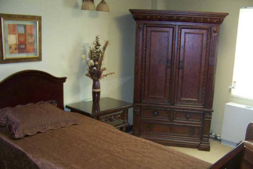 Bed and armoire in room at PARCway Post Acute Recovery Center in Oklahoma City, OK