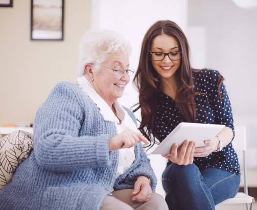 A granddaughter shows her beloved grandmother how to use an iPad at Cottagewood Senior Communities