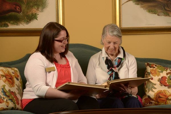 Caregiver and resident reading at Symphony at St. Augustine in St Augustine, Florida