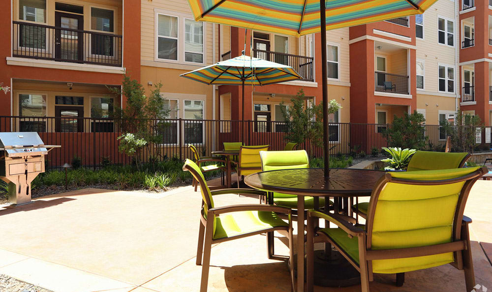 Outdoor furniture and umbrella offering shade near the 4000 Hulen Urban Apartment Homes pool area