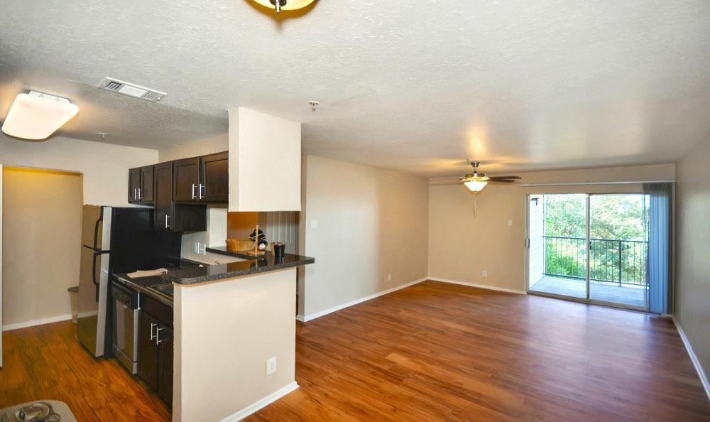 Kitchen and living room at  Fountains at Steeplechase Apartments in Plano, TX