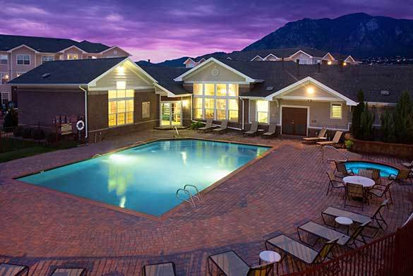 Pool and sun deck at twilight at Westmeadow Peaks Apartments in Colorado Springs, CO