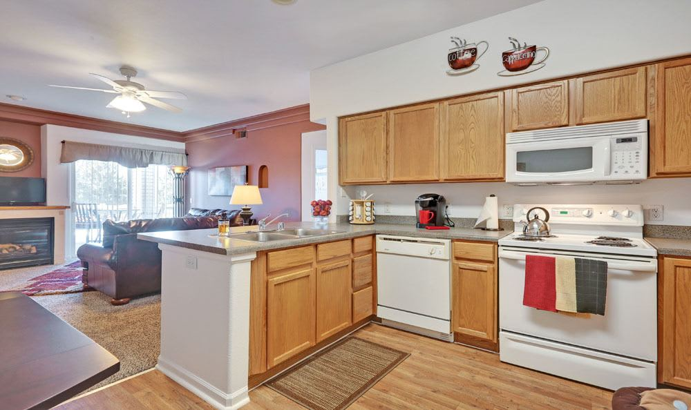 Kitchen with white appliances at Vistas at Stony Creek Apartments in Littleton, Colorado