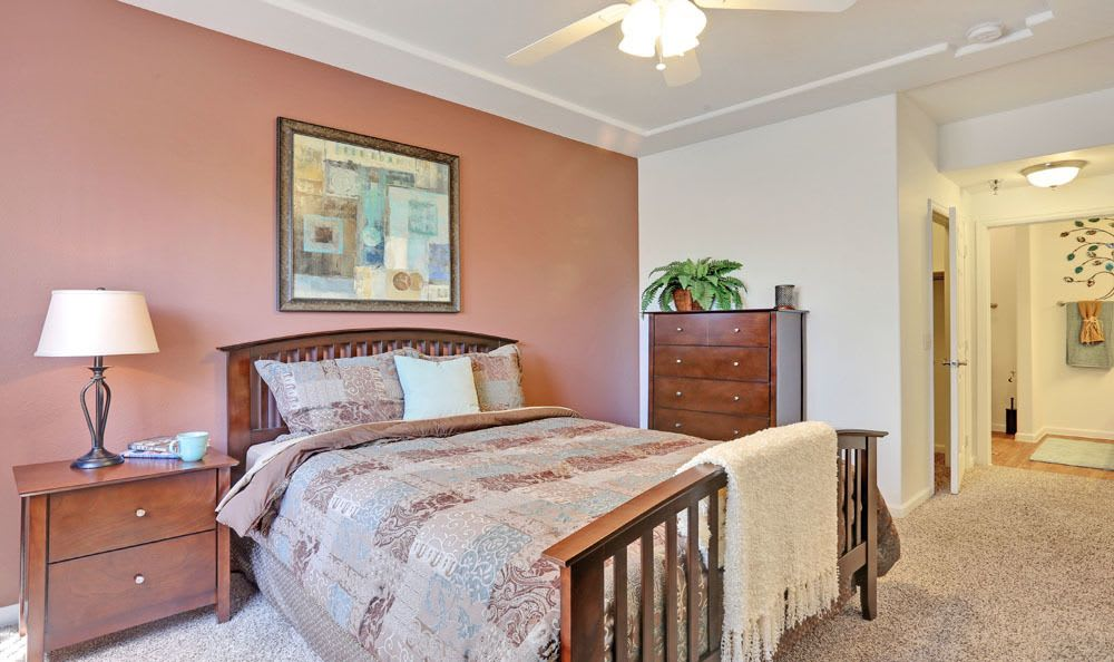 Model bedroom featuring a ceiling fan at Vistas at Stony Creek Apartments in Littleton, Colorado
