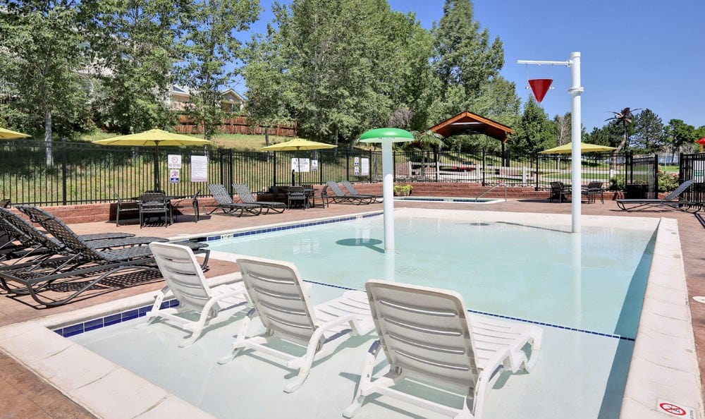 Lounge area by the elegant swimming pool at Vistas at Stony Creek Apartments in Littleton, Colorado
