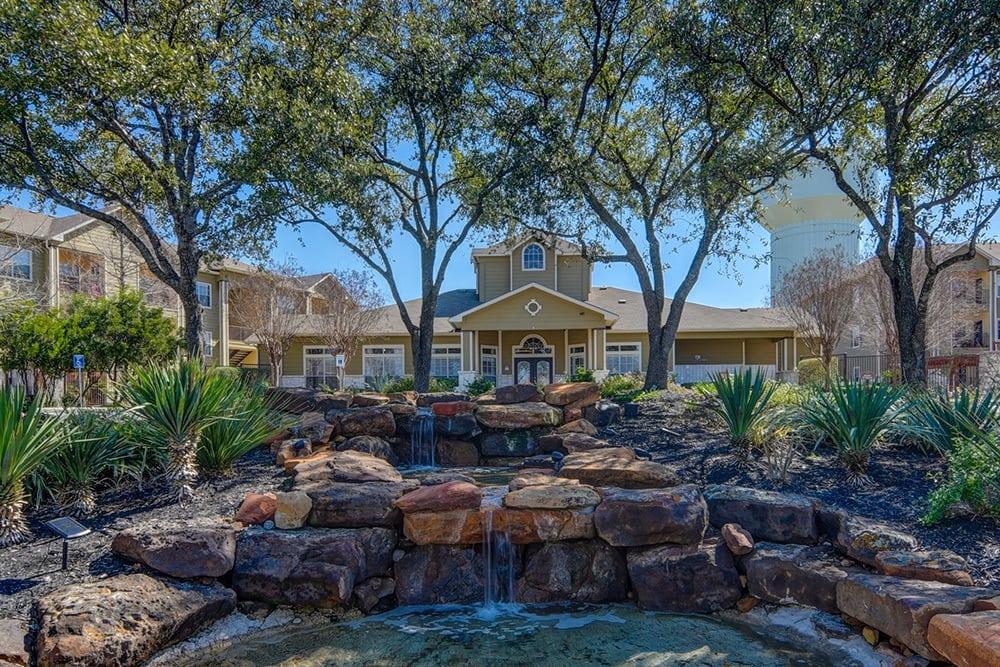 Facade and pond at The BLVD at Medical Center Apartments in San Antonio, TX