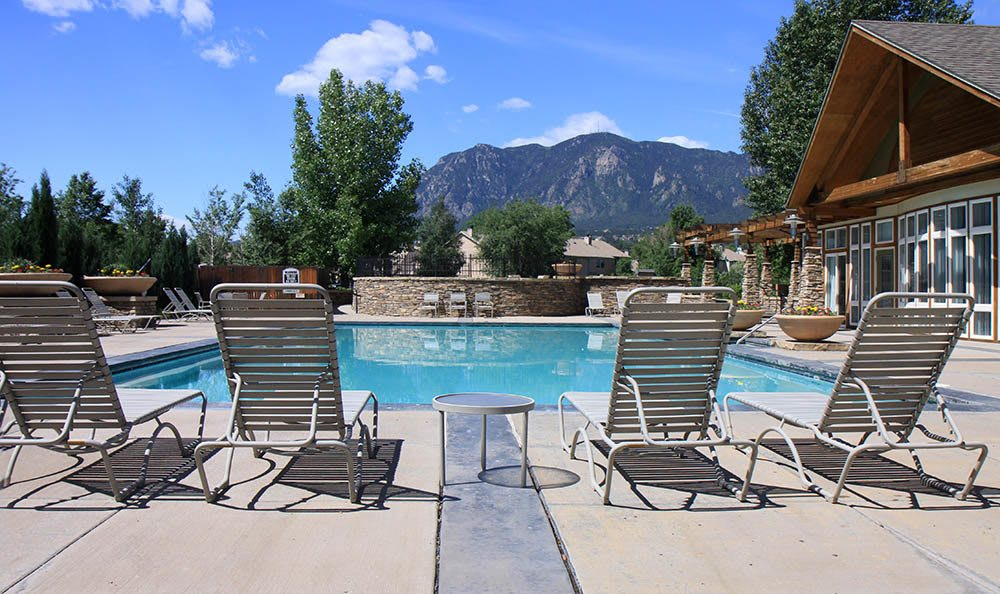 Lounge chairs outdoors at Broadmoor Ridge Apartment Homes swimming pool