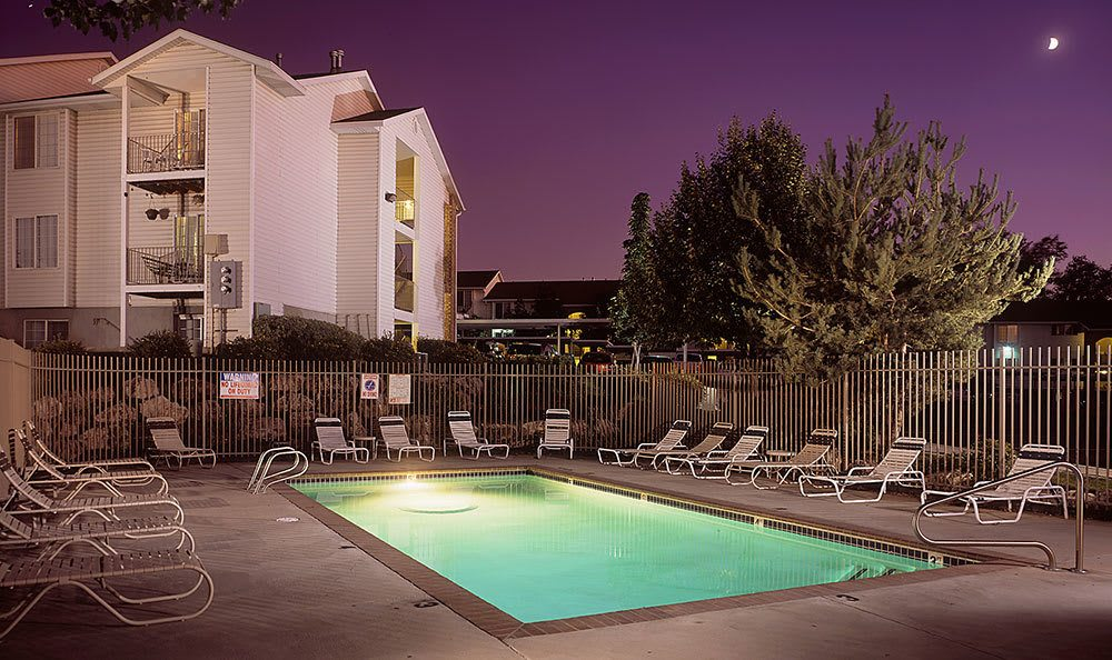 Lighted swimming pool at night at our Bountiful apartments