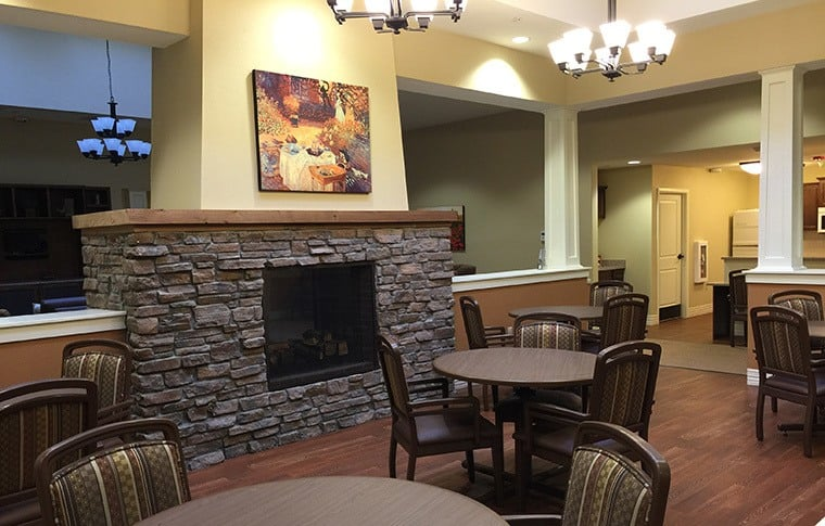 The dining area here at New Dawn Memory Care has a fireplace and is beautifully decorated