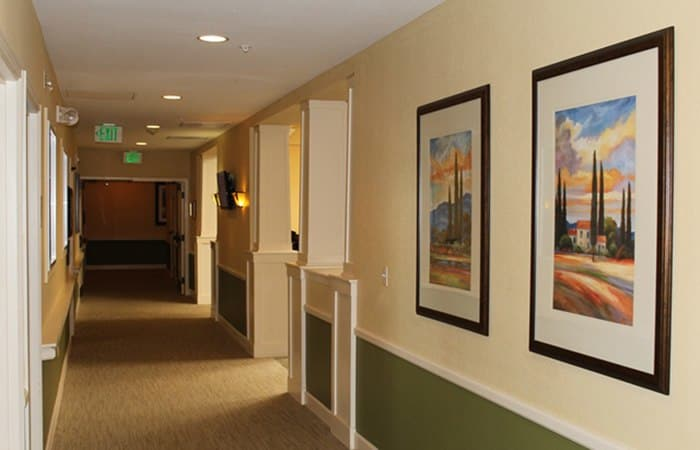 The hallways at New Dawn Memory Care are beautifully carpeted and lined with photos