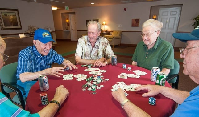 Cards with friends at Bedroom at Pioneer Village, senior living in Jacksonville, OR