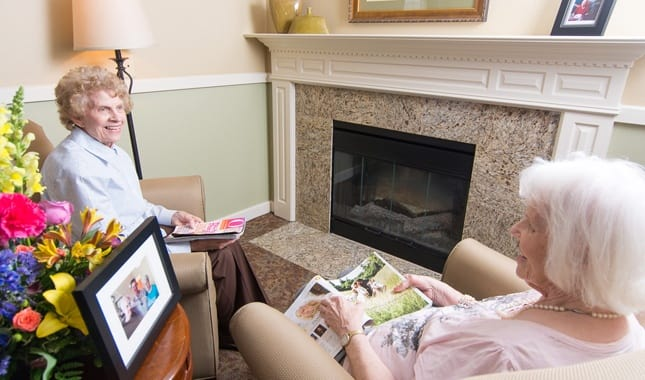 Friends laughing by the fireplace at Farmington Square Beaverton, senior living in Beaverton, OR