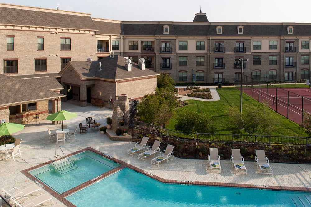 Lewisville senior living features a beautiful pool and tennis courts for residents