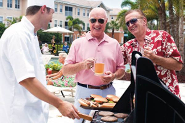 Seniors grilling hamburgers at Discovery Village At The Forum - Independent Living